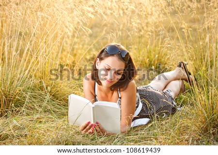 Woman lies on grass and reads book at summer field - stock photo