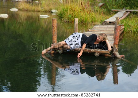 woman lies on the wooden pier - stock photo