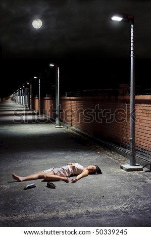 Woman lies vulnerable in the vacant street - stock photo