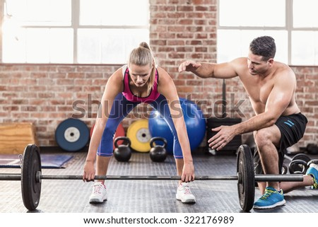 Woman lifting barbell with her trainer in crossfit gym - stock photo