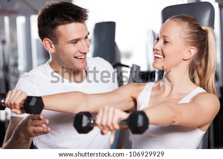 Woman lifting dumbbells while instructor assisting her