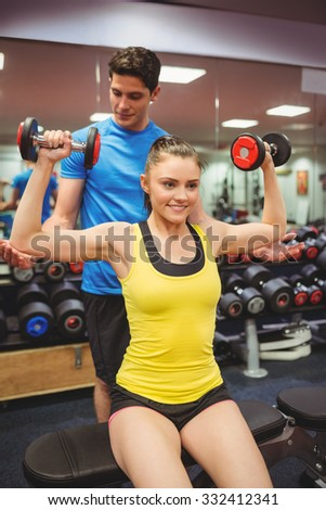 Woman lifting dumbbells with her trainer at the gym