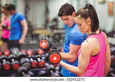 Woman lifting dumbbells with her trainer the gym - stock photo