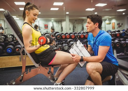 Woman lifting dumbbells with her trainer the gym