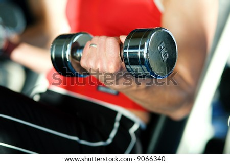 Woman lifting hand weights in a gym, focus on hand of woman and front of dumbbell - stock photo