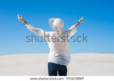 Woman lifting her hands up in the air standing on sand dune - stock photo