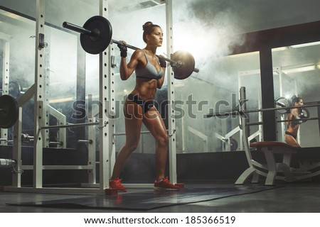 Woman lifting weight in gym - stock photo