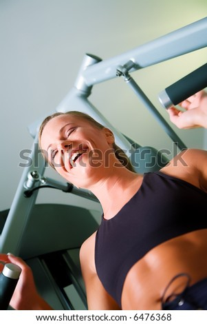 Woman lifting weights in a gym, smiling, having fun - stock photo