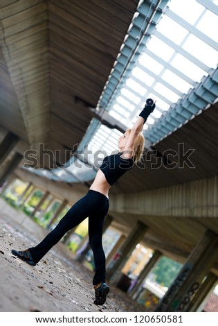 Woman lifting weights in urban setting - stock photo
