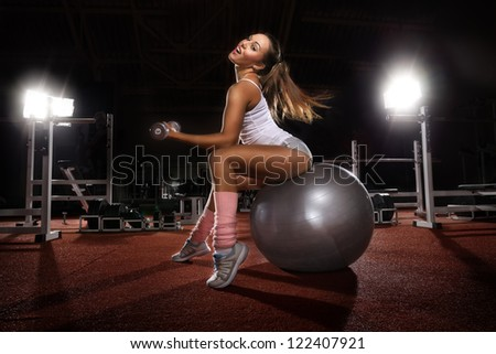Woman Lifting Weights on Pilates ball workout posture in fitness club - stock photo