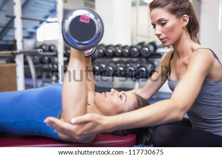 Woman lifting weights with female trainer in gym - stock photo