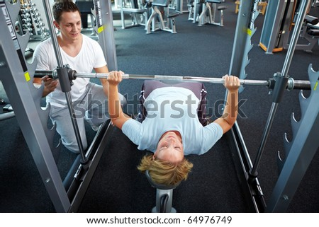 Woman lifting weights with personal trainer in a gym - stock photo