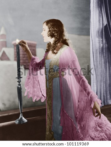 Woman lighting candle on winter evening - stock photo