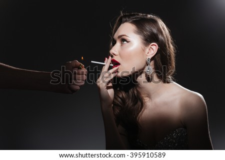 Woman lighting cigarette on black background