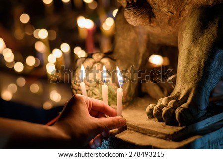 Woman lighting prayer candle in temple - stock photo