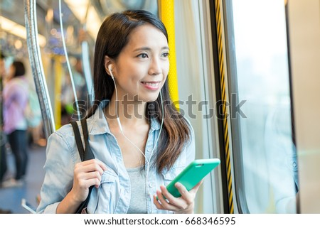 Woman listen to music with cellphone on train