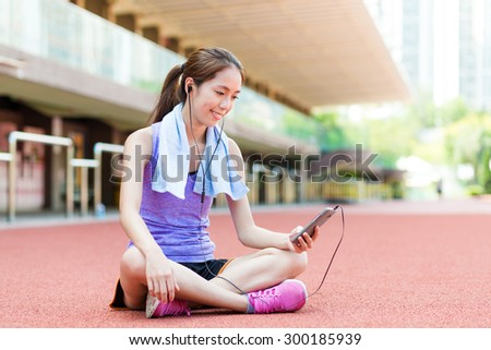 Woman listen to song and sitting on sport stadium - stock photo