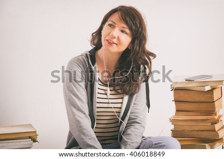 Woman listening an audiobook on smartphone sitting between piles of paper books on the floor - stock photo