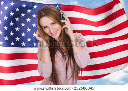 Woman Listening English Language Learning Course Audiobook In Front Of American Flag - stock photo