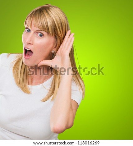 Woman Listening Gossip against a green background - stock photo