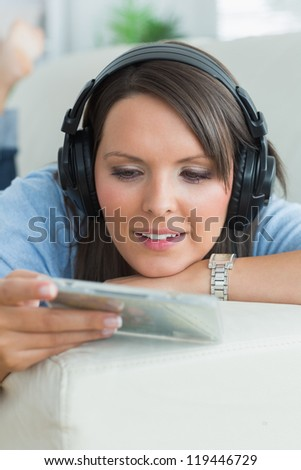Woman listening music and looking at cd on sofa in the living room - stock photo