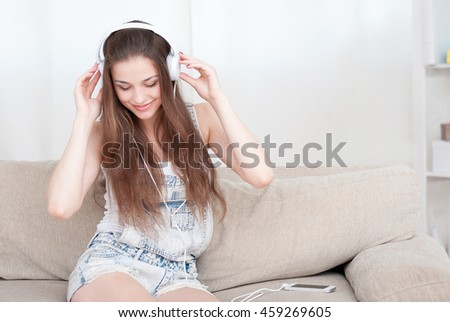 Woman listening music in headphones sitting on sofa in room