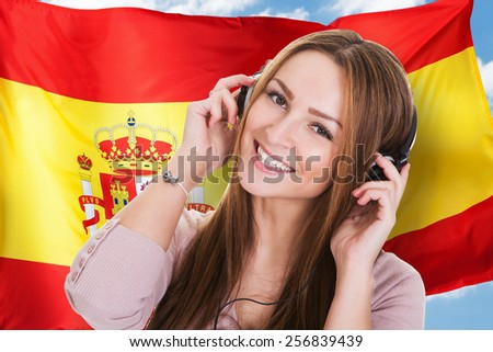 Woman Listening Spanish Learning Audiobook In Front Of Spanish Flag - stock photo