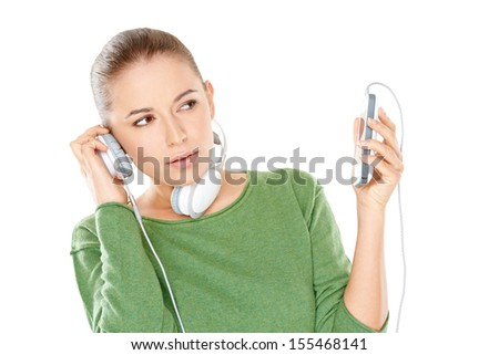 Woman listening to a new music download on her headphones with a critical expression unsure whether she approves or not - stock photo