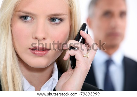 Woman listening to messages on her phone - stock photo