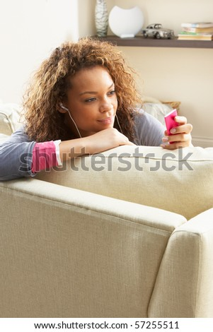 Woman Listening To MP3 Player On Headphones Relaxing Sitting On Rug At Home - stock photo