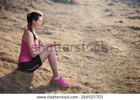Woman listening to mp3 player whilst sitting on the grass - stock photo