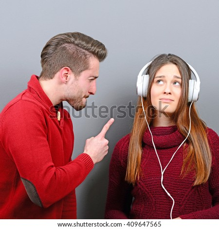 Woman listening to music and doesnt care about him screaming at her - stock photo