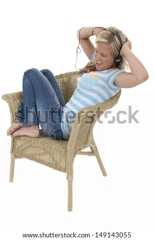 Woman listening to music casual, relaxed in chair - stock photo