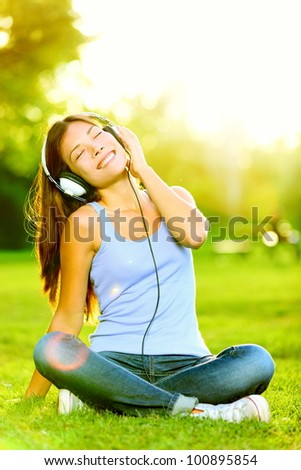 Woman listening to music. Female student girl outside in park listening to music on headphones while studying. Happy young university student of mixed Asian and Caucasian ethnicity.