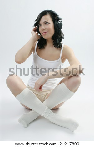 Woman listening to music, in white. studio shot