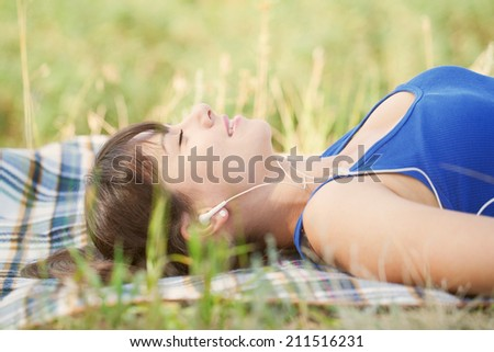 Woman listening to music lying on the grass in the park. - stock photo