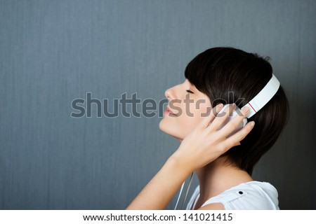 Woman listening to music on earphones with her hands to her ears and eyes closed in pleasure and bliss, profile head and shoulders portrait with copyspace - stock photo