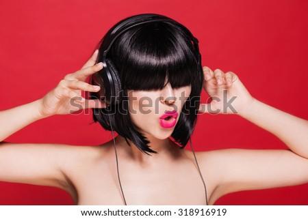 Woman listening to music on headphones enjoying a dance. - stock photo