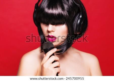 Woman listening to music on headphones enjoying a singing. Closeup portrait of beautiful girl with pink lips. Karaoke - stock photo