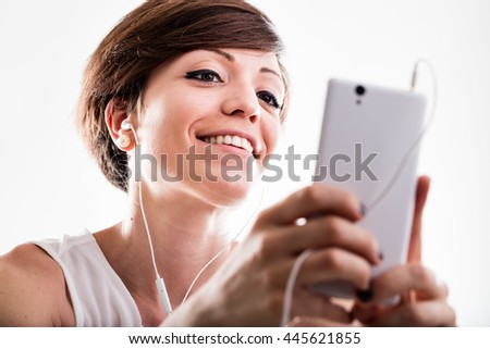 Woman listening to music on her mobile phone using an earplug searching on the screen for her favorite tune, close up low angle view