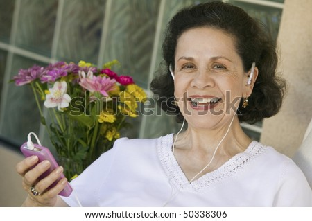 Woman Listening to Music on MP3 Player - stock photo