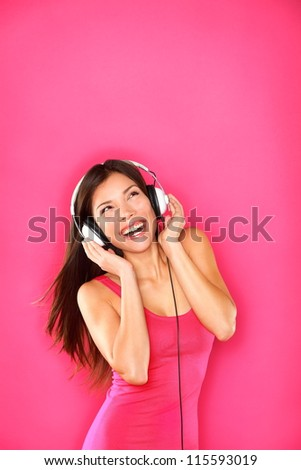 Woman listening to music wearing headphones dancing happy smiling and joyful on pink background. Funky fresh multiracial Caucasian / Asian Chinese female model - stock photo