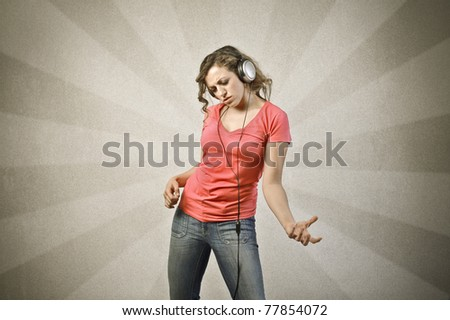 Woman listening to music while playing an invisible guitar - stock photo