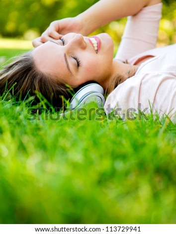 Woman listening to music with headphones at the park - stock photo