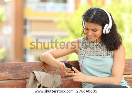 Woman listening to the music from a smart phone with headphones in a park - stock photo