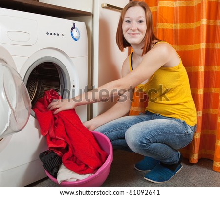 Woman loading the washing machine at her home - stock photo