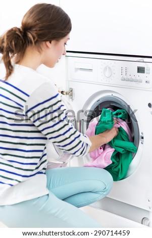 Woman loading washing machine - stock photo