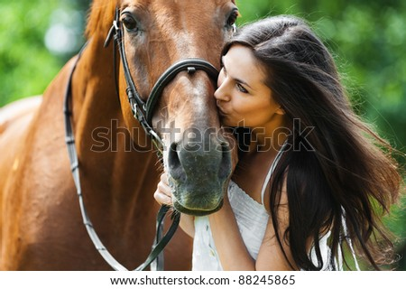 woman long hair kissing beautiful horse - stock photo