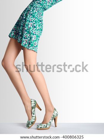 Woman long legs in fashion dress and high heels. Perfect female sexy legs, stylish green flower skirt and summer glamour shoes. Unusual creative elegant walking out outfit, people.  Vintage,copy space - stock photo