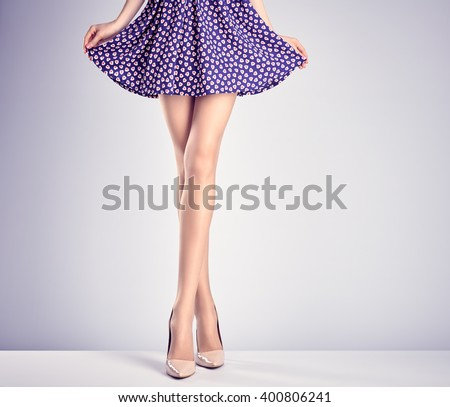 Woman long legs in fashion dress and high heels. Perfect female  sexy legs, stylish purple skirt and summer glamour shoes. Unusual creative elegant walking out outfit, people.  Vintage, copy space - stock photo